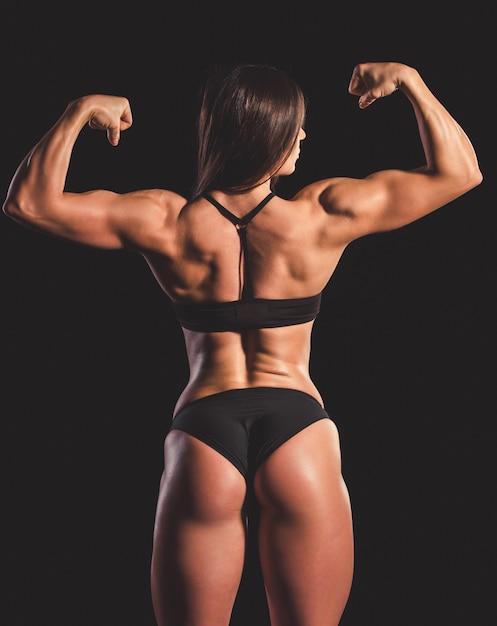 Mujer en ropa interior negra mostrando sus músculos Foto Premium