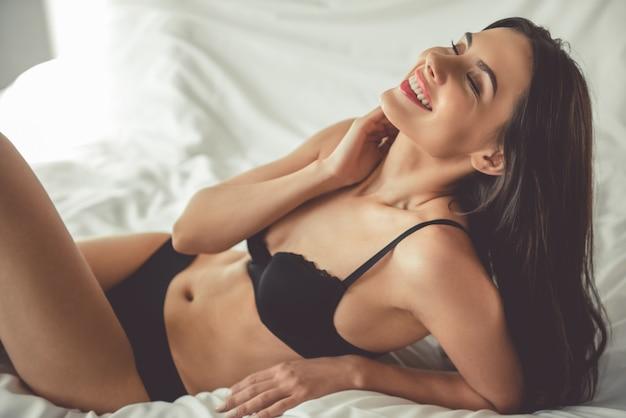 Mujer En Ropa Interior Negro Está Sonriendo Mientras Está