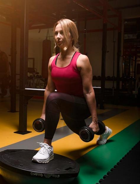 Mujer en rosa haciendo entrenamiento de piernas con mancuernas en un gimnasio. Foto gratis