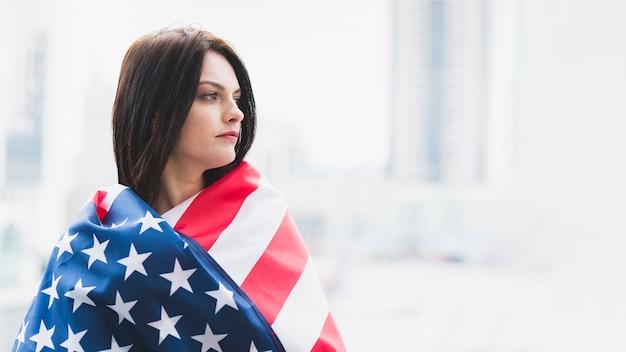 Mujer de rostro sombrío envuelta en bandera americana. Foto gratis