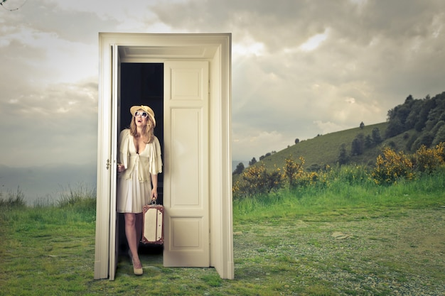 Mujer rubia abriendo una puerta Foto Premium