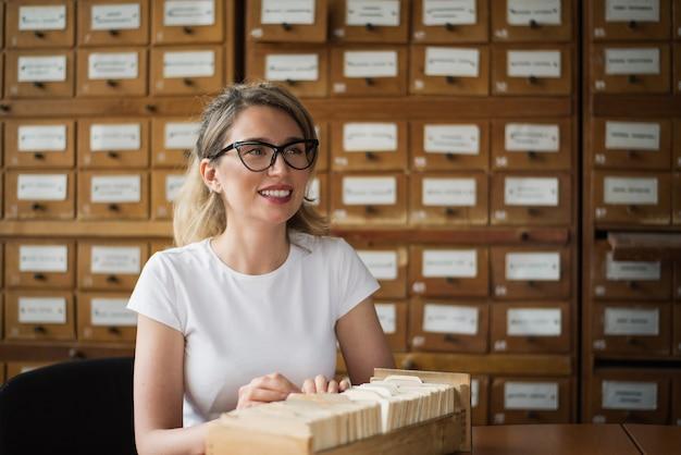 d44f9ce9 Mujer rubia buscando archivos de libros en la biblioteca | Descargar ...