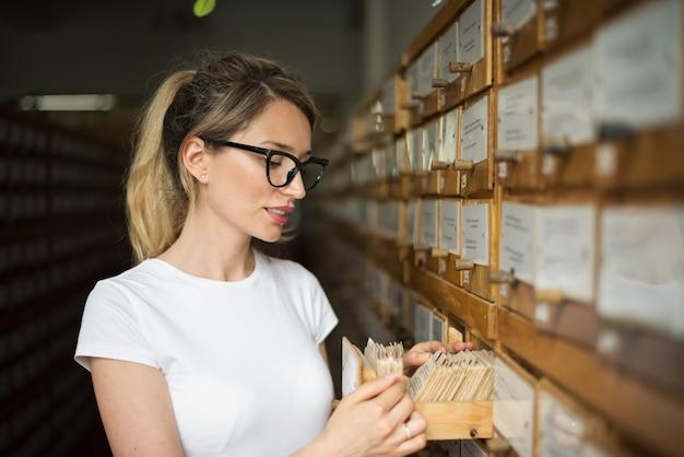 1d99da5a Mujer rubia buscando archivos de libros en catálogo viejo ...