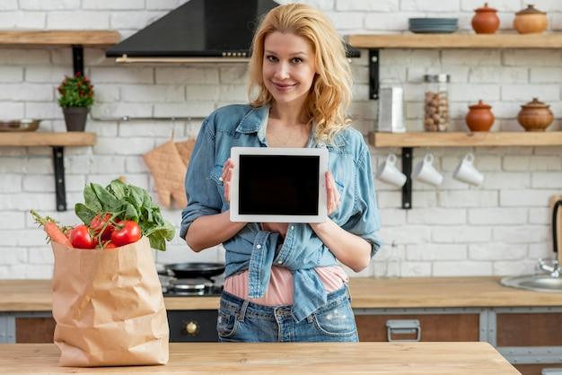 Mujer rubia en la cocina con una tablet Foto gratis