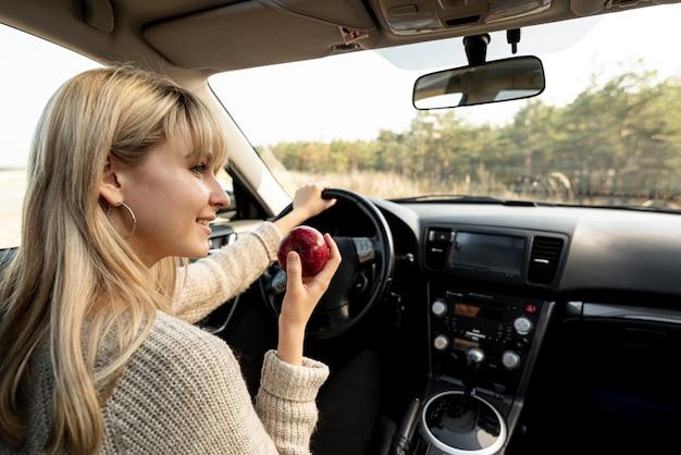 Mujer rubia conduciendo y comiendo una deliciosa manzana Foto gratis