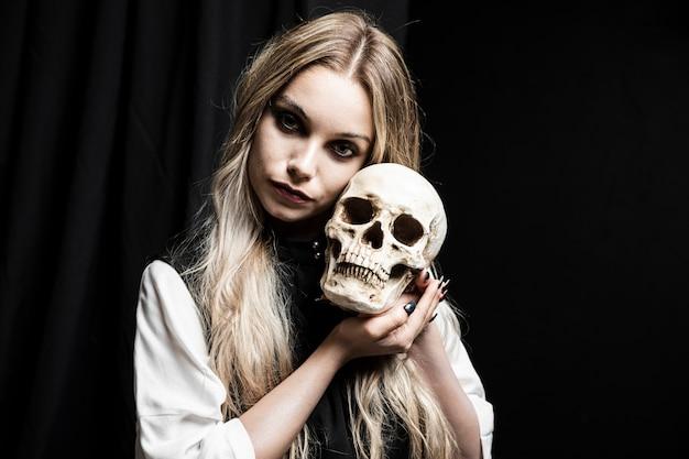Mujer rubia con cráneo humano Foto gratis