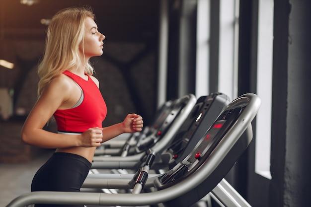 Mujer rubia deportiva en un entrenamiento de ropa deportiva en un gimnasio Foto gratis