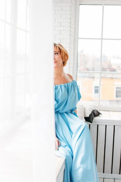 Mujer rubia encantadora sonriente joven del pelo corto en el vestido largo del verano azul que se sienta en travesaño de la ventana Foto Premium