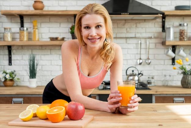 Mujer rubia con frutas en la cocina Foto gratis