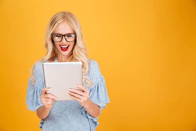 Mujer rubia joven feliz que usa la tableta. Foto gratis