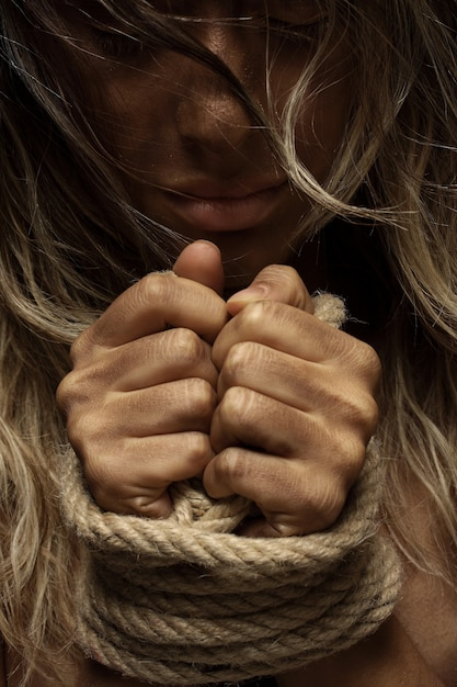 Mujer rubia con las manos atadas Foto gratis