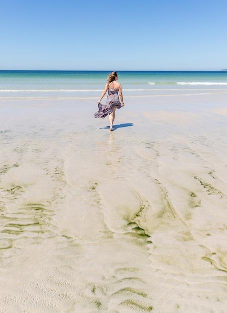 Mujer rubia de mediana edad con un vestido caminando por la playa Foto Premium