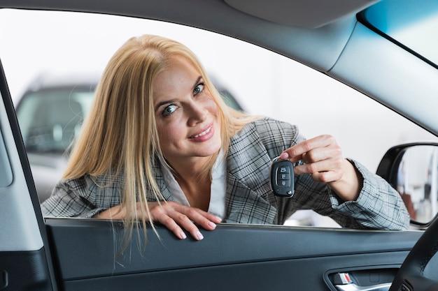 Mujer rubia que sostiene las llaves del coche mirando a la cámara Foto gratis