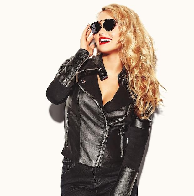 Mujer rubia en ropa casual negra con labios rojos y gafas de sol Foto gratis