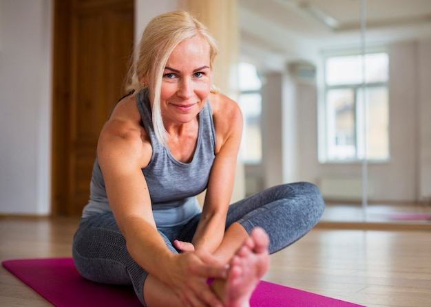 Mujer rubia sonriente haciendo pilates Foto gratis