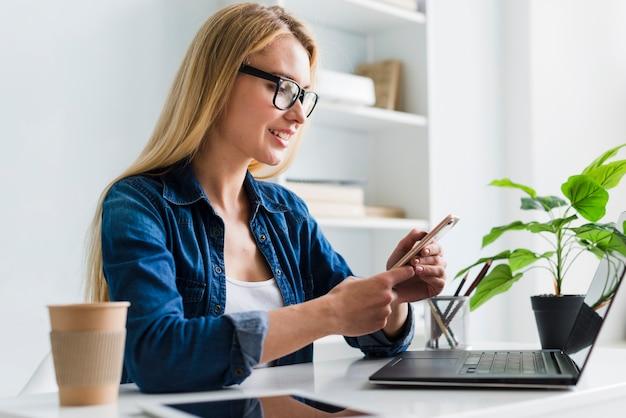 Mujer rubia trabajando e interactuando con smartphone Foto gratis