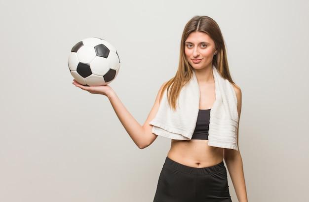 Mujer rusa de la aptitud joven que lleva a cabo algo con la mano. sosteniendo un balón de fútbol. Foto Premium