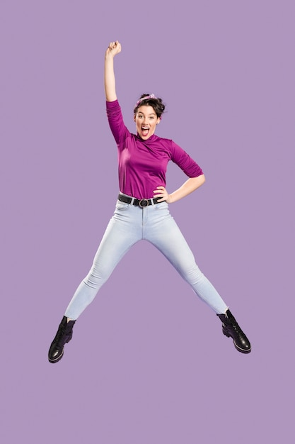 Mujer saltando y con un brazo sobre su cabeza Foto gratis