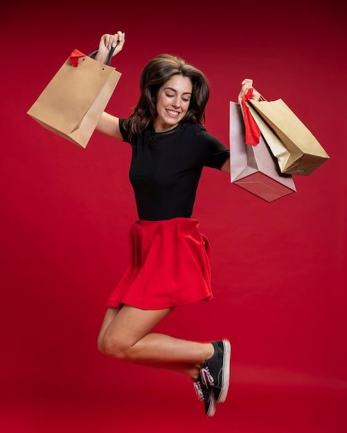 Mujer saltando mientras sostiene sus bolsas de compras Foto Premium