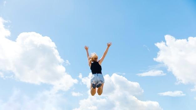 Mujer saltando sobre fondo de cielo azul Foto gratis