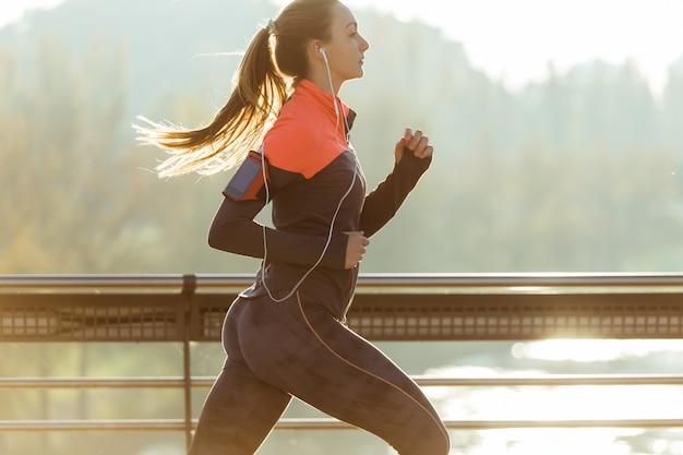 Mujer saludable corriendo con fondo borroso Foto Premium