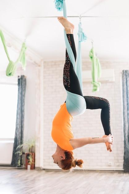 Mujer sana haciendo yoga aérea con estiramiento de pierna Foto gratis