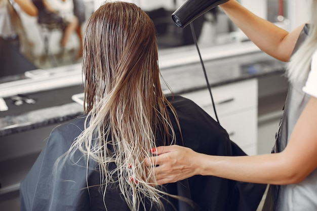 Mujer secando el cabello en una peluquería Foto gratis