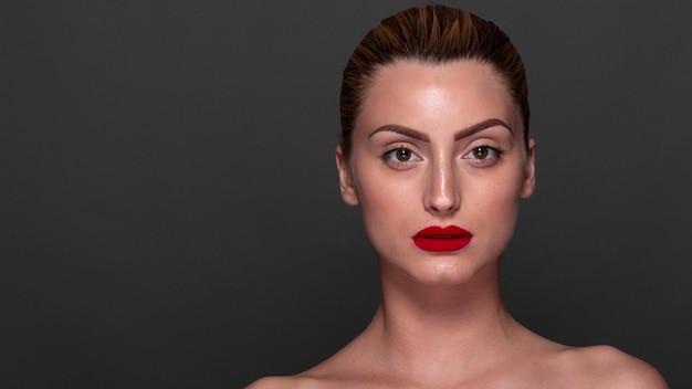Mujer segura con lápiz labial rojo en Foto gratis