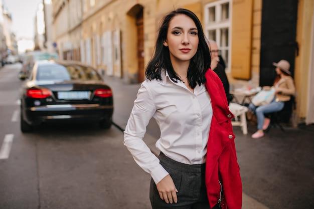 Mujer segura de pelo negro posando en la calle con coche en la pared Foto gratis