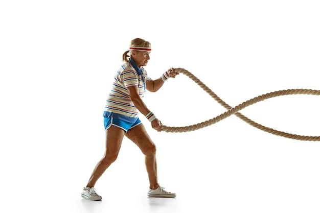 Mujer senior entrenando con cuerdas en ropa deportiva sobre pared blanca Foto gratis