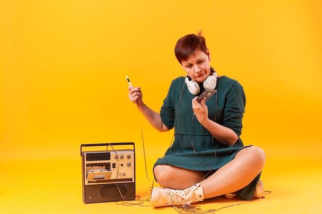 Mujer senior hipster mirando un cassette Foto gratis