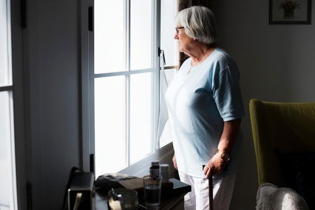 Mujer senior parado solo en casa Foto gratis