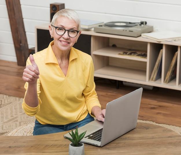 Mujer senior sonriente de alto ángulo usando una computadora portátil Foto gratis