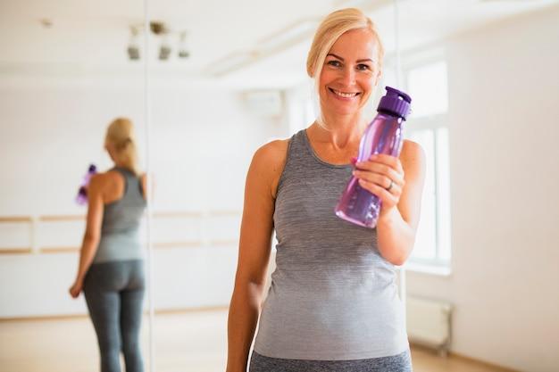 Mujer senior sonriente sosteniendo una botella de agua Foto gratis