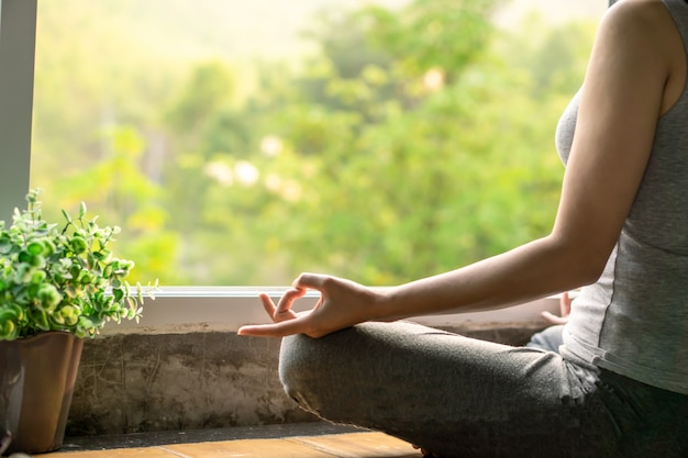 Mujer sentada al lado de la ventana haciendo yoga Foto Premium