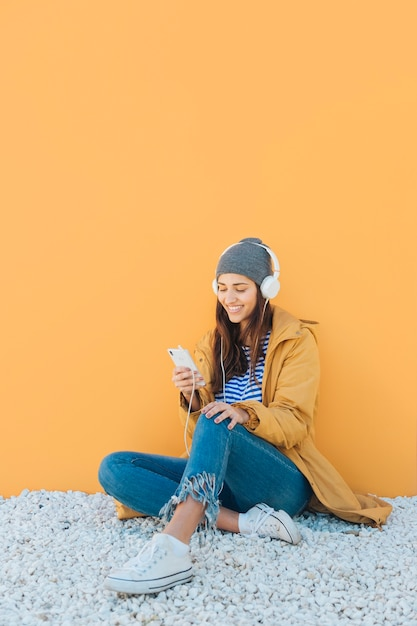 Mujer sentada en la alfombra escuchando música con auriculares usando teléfono celular Foto gratis