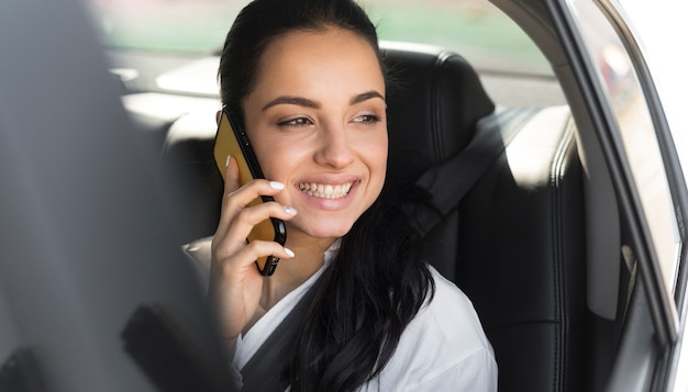 Mujer sentada en un auto y hablando por teléfono Foto gratis