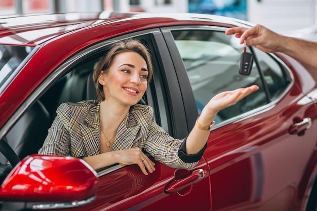 Mujer sentada en auto rojo y recibiendo llaves Foto gratis