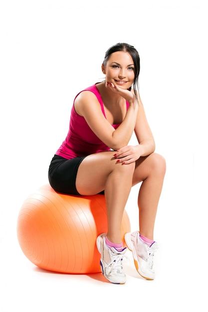 Mujer sentada en el balón Foto gratis
