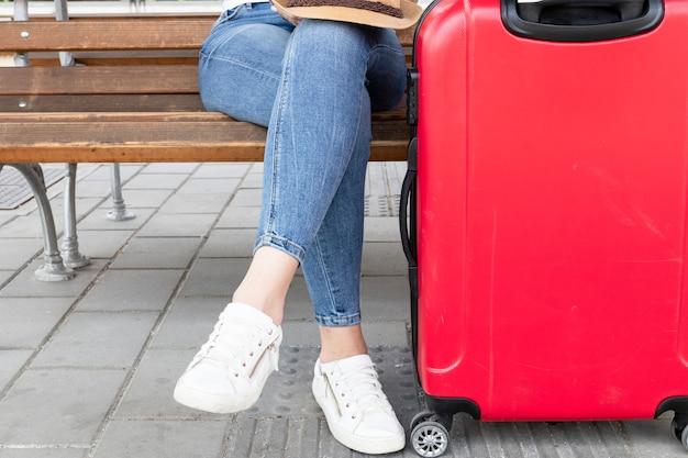 Mujer sentada en un banco con equipaje Foto gratis