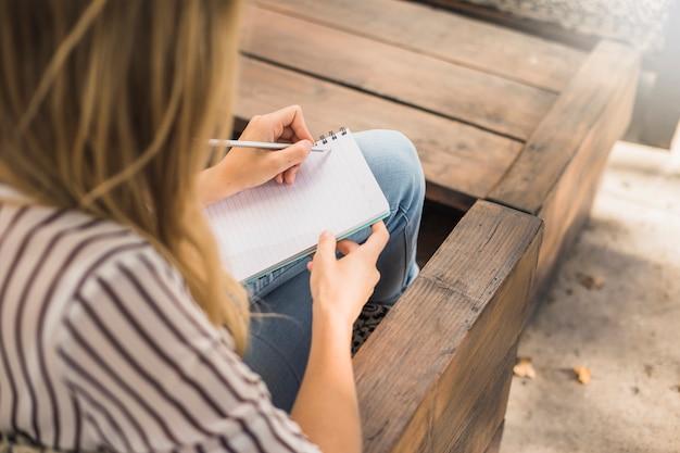 Mujer sentada en el banco escribiendo sobre cuaderno con lápiz Foto gratis