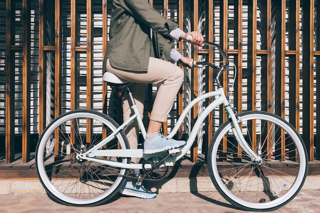 Mujer sentada en la bicicleta de la ciudad al aire libre Foto Premium