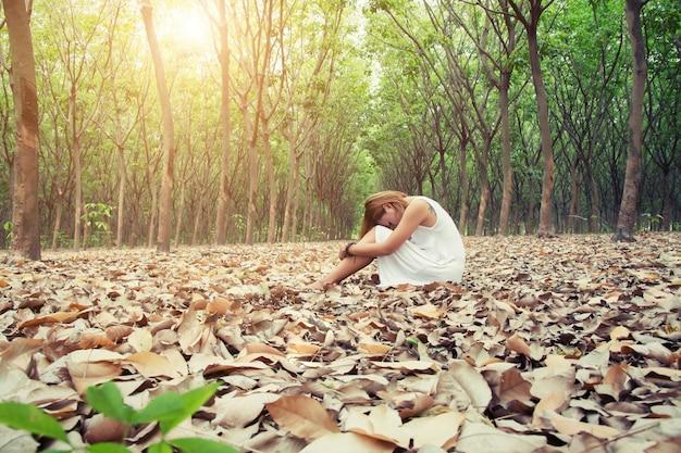 Mujer sentada con la cabeza descansando en sus rodillas Foto gratis