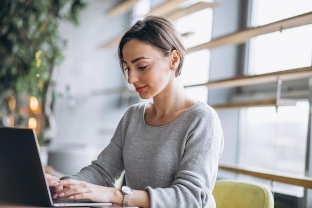 Mujer sentada en un café tomando café y trabajando en una computadora Foto gratis