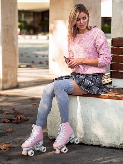 Mujer sentada con calcetines y patines Foto gratis