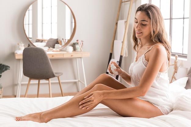 Mujer sentada en la cama y masajeando sus piernas Foto gratis