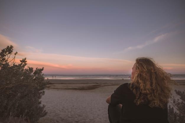 Mujer sentada cerca de la costa del mar y mirando la puesta del sol Foto gratis