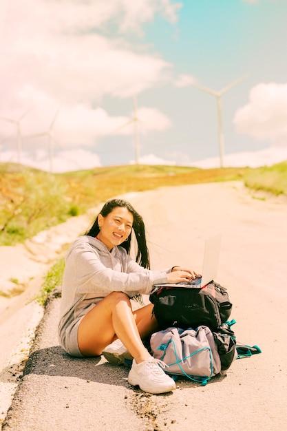 Mujer sentada en el costado del camino y trabajando en la computadora portátil colocada en las mochilas Foto gratis
