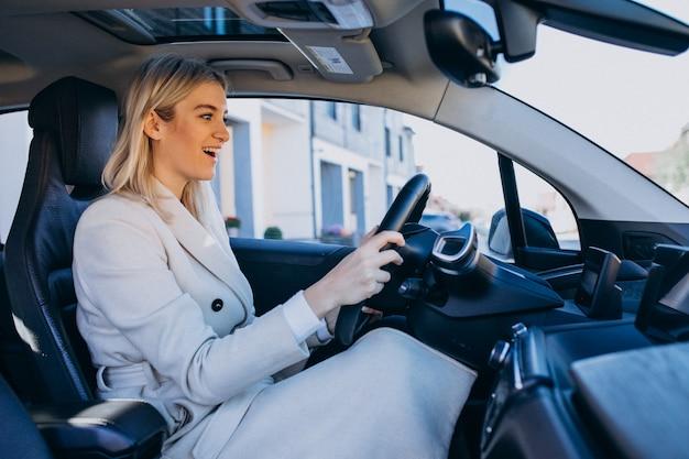 Mujer sentada dentro del auto eléctrico mientras carga Foto gratis