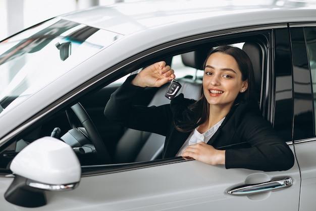 Mujer sentada dentro de un auto y sosteniendo las llaves Foto gratis